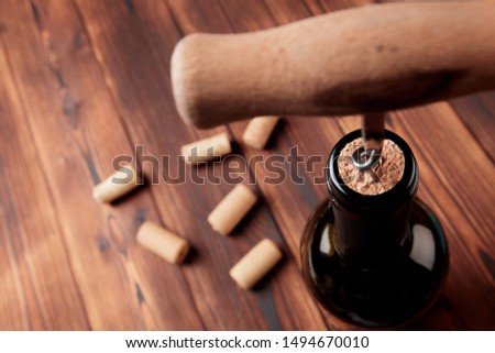 Corkscrew and bottle of wine on the board #1494670010