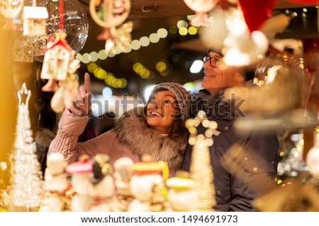 shopping, winter holidays and people concept - happy senior couple at christmas market souvenir shop on town hall square in tallinn, estonia #1494691973