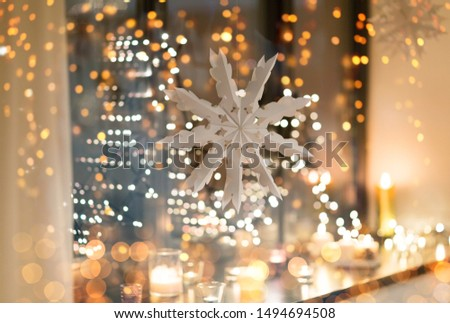 christmas and holidays concept - paper snowflake decoration hanging over garland lights and candles at night window #1494694508