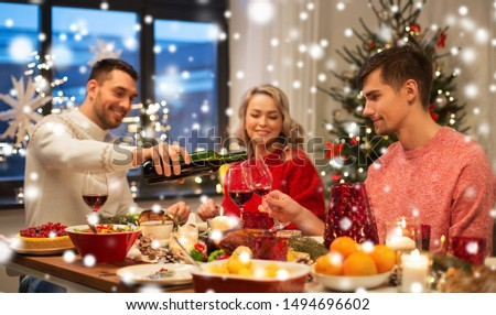 holidays and celebration concept - happy friends having christmas dinner at home and drinking red wine over snow #1494696602