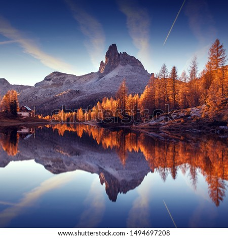 Wonderful autumn landscape during sunset. Fairy tale moutain lake with picturesque sky, majestic rocky mount and colorful trees glowing sunlight. Amazing nature scenery. Federa lake. Dolomites Alps. #1494697208