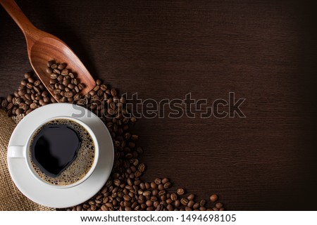 coffee cup and beans placed on a wooden board With copy space for text.   #1494698105