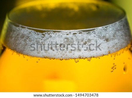 fresh blonde beer poured into a crystal glass. Beer makes a lot of foam. Image with beer in a pleasant light, foam and bubbles. About  beer consumption