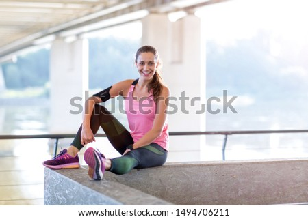 Female runner smiling during urban workout  #1494706211