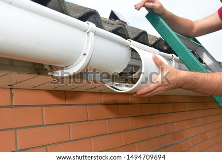 Roof gutter repair. Guttering repair. Roofer contractor repair house rain gutter pipeline.  #1494709694