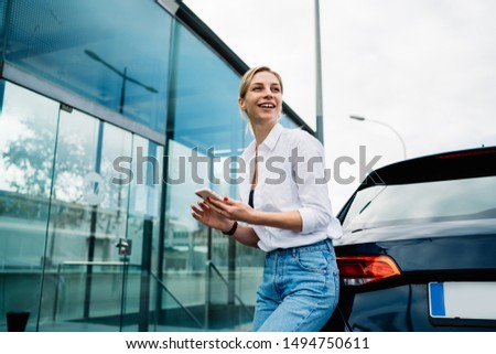 Young cheerful lady in casual outfit leaning on vehicle and looking away with smile while standing in car park and using smartphone #1494750611