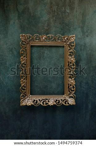 Vintage openwork bronze metal frame on a old wall background