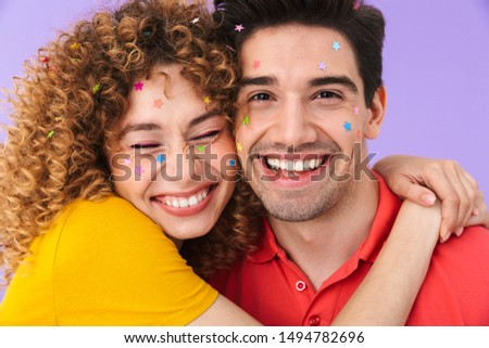 Image of young content couple smiling and hugging while having party with glitter stars on faces isolated over violet background