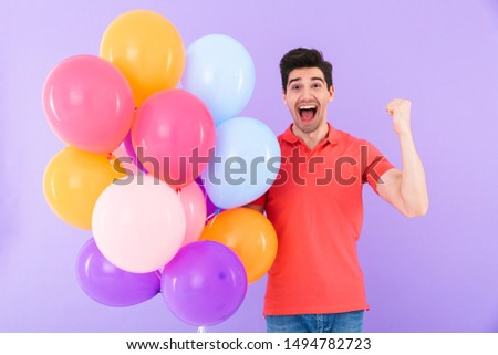 Image of happy delighted man rejoicing while standing with multicolored air balloons isolated over violet background