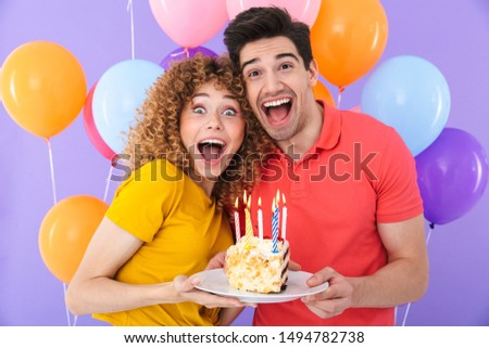 Image of positive couple man and woman celebrating birthday with multicolored air balloons and piece of cake isolated over violet background