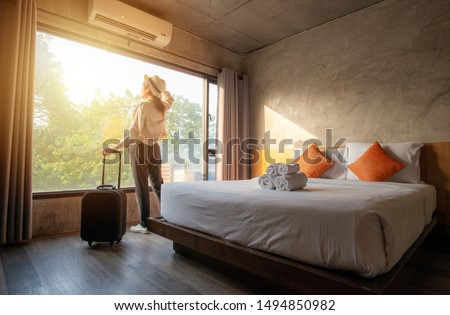 Portrait of tourist woman standing nearly window, looking to beautiful view with her luggage in hotel bedroom after check-in. Conceptual of travel and vacation. Royalty-Free Stock Photo #1494850982