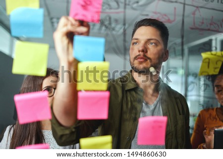Concentrated male executive discussing business ideas with colleagues by writing on sticky notes pasted over the glass board #1494860630