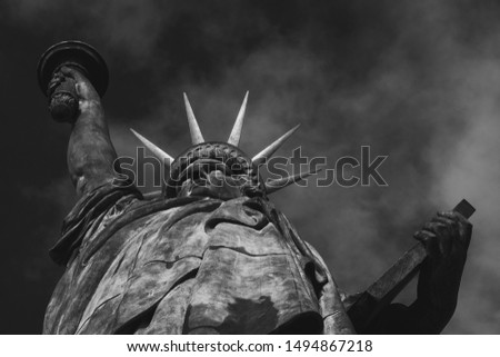 Freedom symbol. Statue of Liberty at Isle of the Swans in Paris (France) against sky with clouds at background. Bottom view. Black and white photo. #1494867218