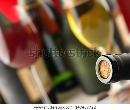 Still life with bottles, glasses, focus on a bottle with a cork