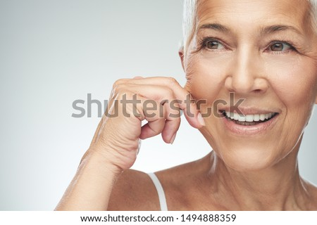 Gorgeous smiling Caucasian senior woman with short gray hair pinching her cheek. Beauty photography. #1494888359