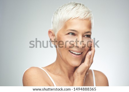 Beautiful smiling senior woman with short gray hair posing in front of gray background. Beauty photography. #1494888365