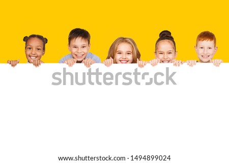 Happy children with empty board for your text isolated over yellow background, copy space Royalty-Free Stock Photo #1494899024