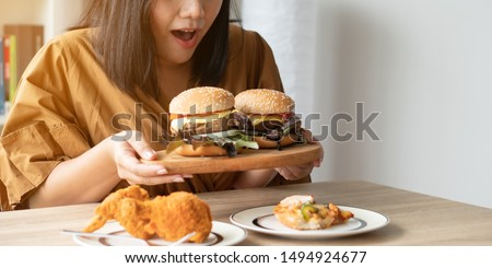 Hungry overweight woman holding hamburger on wooden plate, Fried chicken and Pizza on table .Concept of binge eating disorder (BED). #1494924677