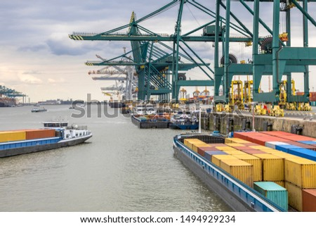 Loaded ships in busy port of Antwerp at container terminal with automated cranes and lots of vessels. Belgium #1494929234