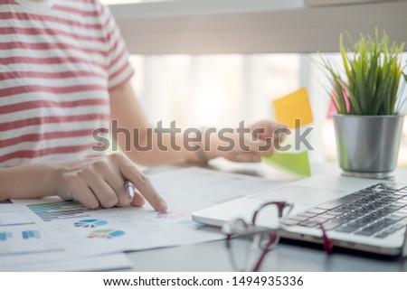 woman or accountant hand holding pen working point graph business data, accountancy document and laptop computer at office, business concept #1494935336