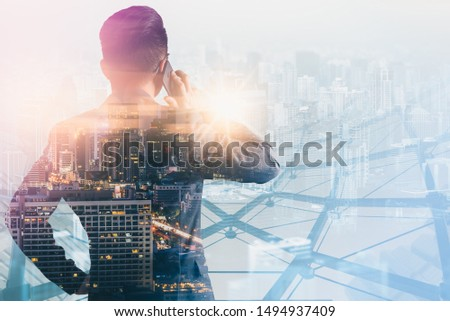 The double exposure image of the business man using a smartphone during sunrise overlay with cityscape image. The concept of modern life, business, city life and internet of things. #1494937409