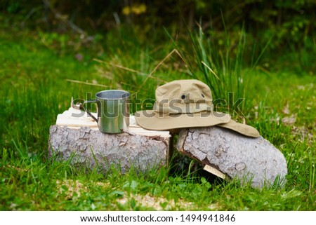 tourism day. tin mug and hat with wide brim sun protective lie on a log in the forest #1494941846