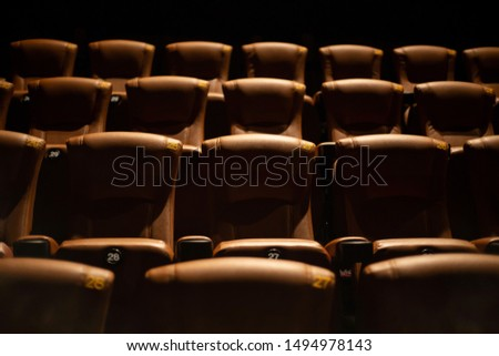 brown special leather seat in movie theater. pattern of many armchairs in dark room . #1494978143