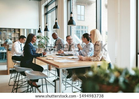 Smiling group of diverse businesspeople discussing paperwork together while having a meeting around a table in a modern office #1494983738