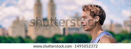 Wireless earbuds man walking running in Central Park New York city listening to music with wearable technology bluetooth earphone earpods panoramic banner. Royalty-Free Stock Photo #1495052372