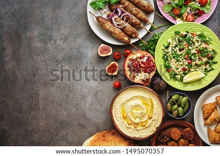 Arabic and Middle Eastern dinner table. Hummus, tabbouleh salad, Fattoush salad, pita, meat kebab, falafel, baklava, pomegranate. Set of Arabian dishes.Top view, copy space. #1495070357