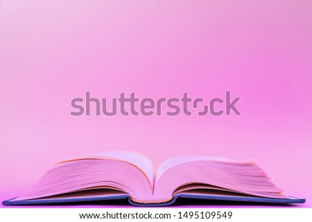 Close-up book on a pastel pink background in a trendy neon color light. The concept of reading, book novelties, book business, literature. Minimalism, place for text. #1495109549