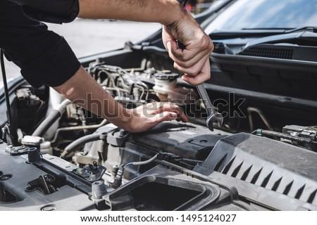 Services car engine machine concept, Automobile mechanic repairman hands repairing a car engine automotive workshop with a wrench, car service and maintenance. #1495124027