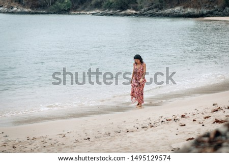 A pensive young lady walks alone the beach alone, looking down at the wet sand and the sea.   #1495129574