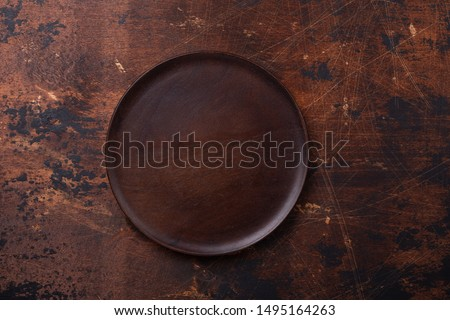 Empty plate and linen napkin on brown wooden background Copy space Top view - Image