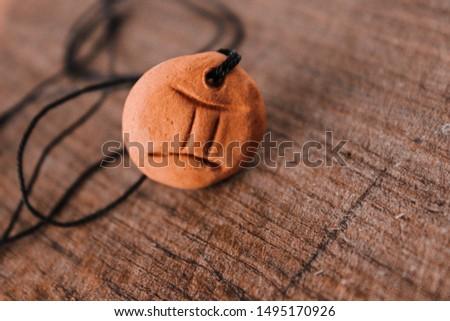 zodiac sign gemini, amulet on a wooden board