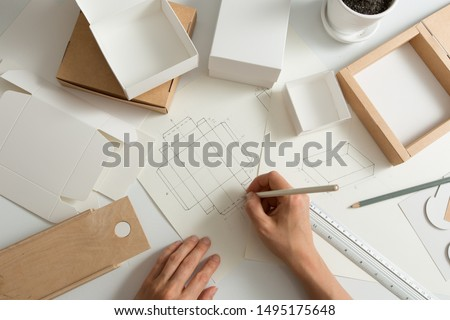 Designer draws a mockup for crafting eco cardboard box. Development a sketch of paper packaging. Royalty-Free Stock Photo #1495175648