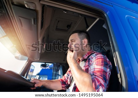 Truck driver yawning while driving. Trucker feeling sleepy and tired after long ride. Overworked people at job. #1495195064