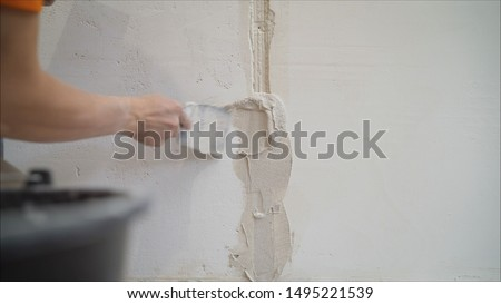 Plastering the wall. Hands Plasterer at work. Application of the plaster on the wall. textured plaster #1495221539
