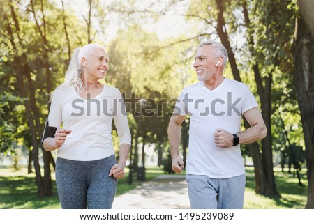 Elderly man and old woman in headphones jogging together outside in park while looking on each other #1495239089