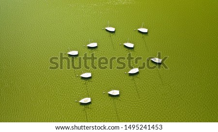 aerial view over ten small, white sail boats with their sails down, with no people, no wind on a lime green colored lake on a sunny morning #1495241453