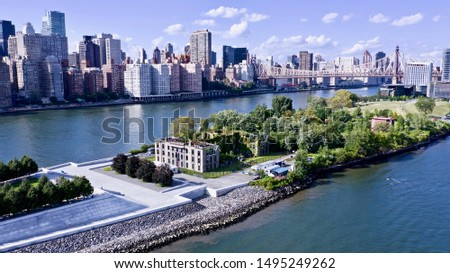 aerial view over the East River in New York City, looking north towards the Queenboro Bridge with Roosevelt Island on the left & the city in the background #1495249262