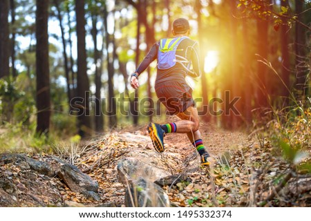 A man Runner of Trail and athlete's feet wearing sports shoes for trail running in the forest Royalty-Free Stock Photo #1495332374