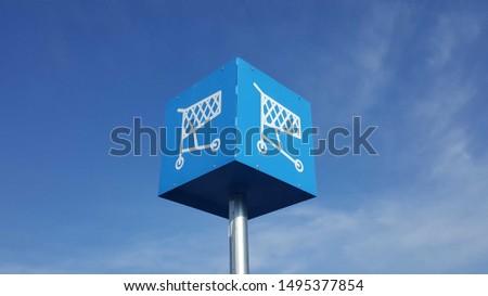 Blue Shopping Cart Return Sign Against a Blue Sky