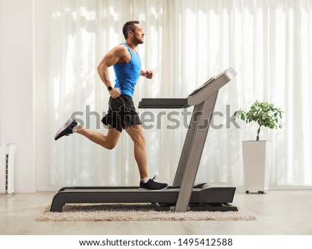 Full length profile shot of a young man running on a treadmill at home  #1495412588