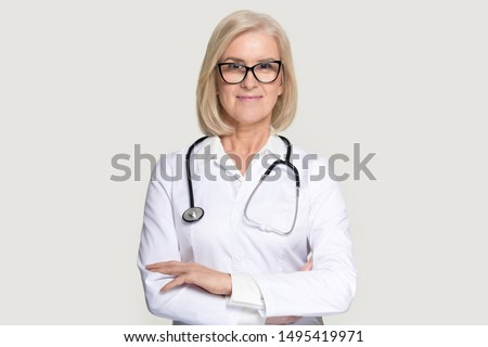 Portrait of senior woman doctor wearing glasses and uniform stand isolated on grey studio background, mature female medical nurse or practitioner with stethoscope look at camera. Healthcare concept #1495419971