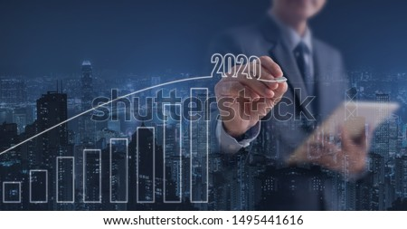 2020 Business Goals, Growth success, real estate development. Double exposure of businessman with digital tablet computer touching on virtual screen and city,  progress of positive business indicator #1495441616