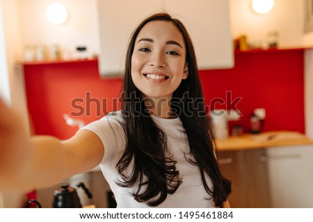 Woman in great mood takes selfie in kitchen. Portrait of brown-eyed girl #1495461884