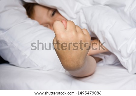 Boy lies in bed and shows fig sign. Focus on hand #1495479086