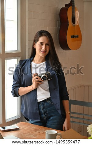 Female holding a camera and looking camera in room. #1495559477