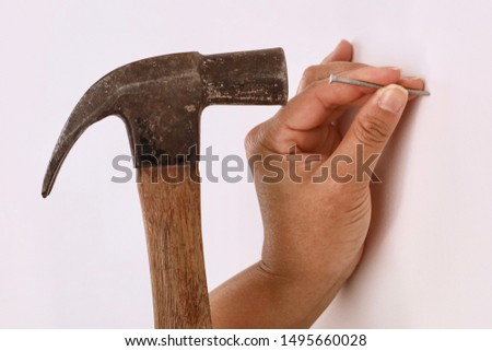 Close-up of a female contractor using a hammer to hammer a nail into a wall #1495660028